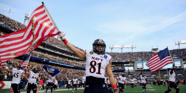 BALTIMORE, MD - DECEMBER 13: Brendan Dudeck #81 of the Navy Midshipmen carries the American flag on the...