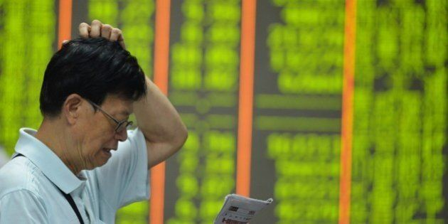 HANGZHOU, CHINA - AUGUST 24: (CHINA OUT) An investor watches the electronic board at a stock exchange...
