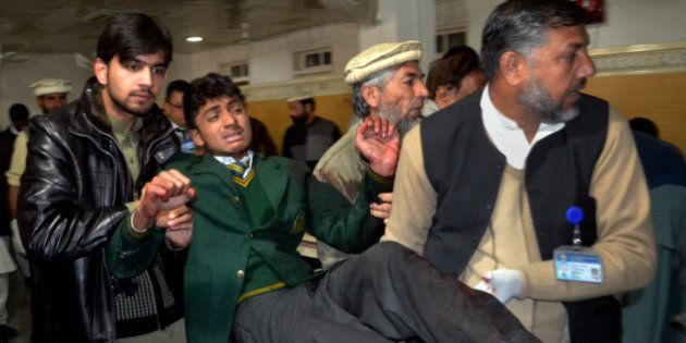 Pakistani volunteers carry a student injured in the shootout at a school under attack by Taliban gunmen,...