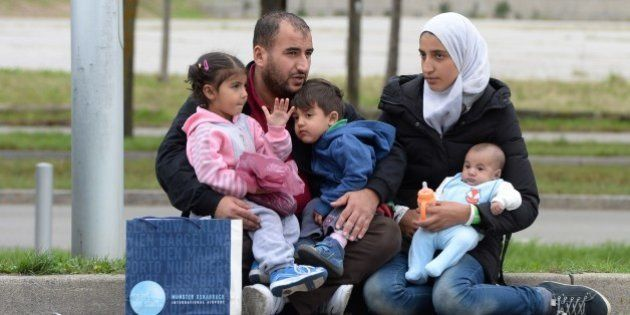 A refugee family from Syria waits in front of a exhibition hall at the Munich fairground that serves...