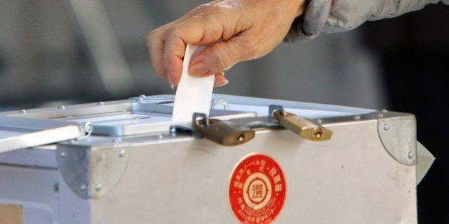 A voter casts a vote in Japan's general election at a polling station in Tokyo on December 14, 2014....