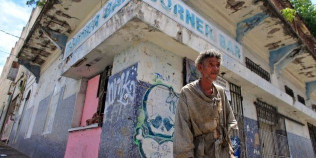 A homeless man stands in front of a closed down business in Puerta de Tierra in the outskirts of Old...