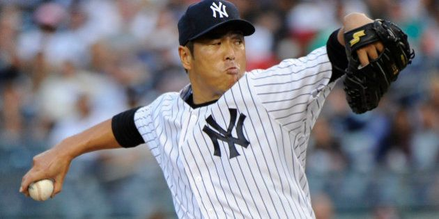 New York Yankees pitcher Hiroki Kuroda delivers the ball to the Toronto Blue Jays during the first inning...