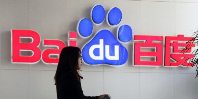 A woman walks past the Baidu Inc. logo in the reception are of the company's headquarters in Beijing,...