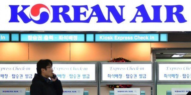 A man talks over his mobile phone in front of the logo of Korean Air at Gimpo airport in Seoul on December...