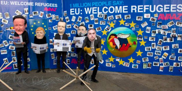 Actors dressed with face masks of EU leaders, from left, British Prime Minister David Cameron, German...