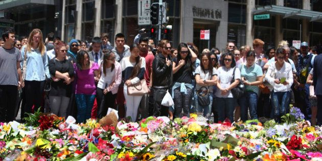 Staff members from the Lindt Chocolat Cafe with their arms linked pay tribute to their colleague who...