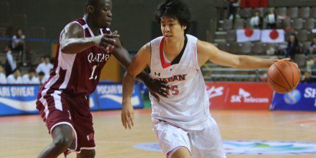 Qatar's Erfan Ali Saeed (L) guards against Japan's Joji Takeuchi (R) in their men's basketball preliminary...