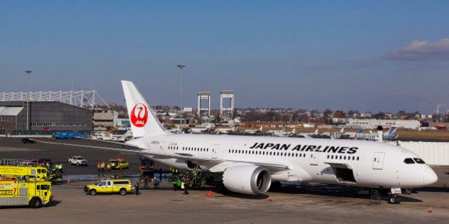 A Japan Airlines Boeing 787 Dreamliner jet aircraft is surrounded by emergency vehicles while parked...
