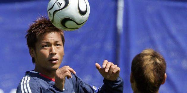 Bonn, GERMANY: Japanese forward Atsushi Yanagisawa (L) heads a ball to teammate Naohiro Takahara during...
