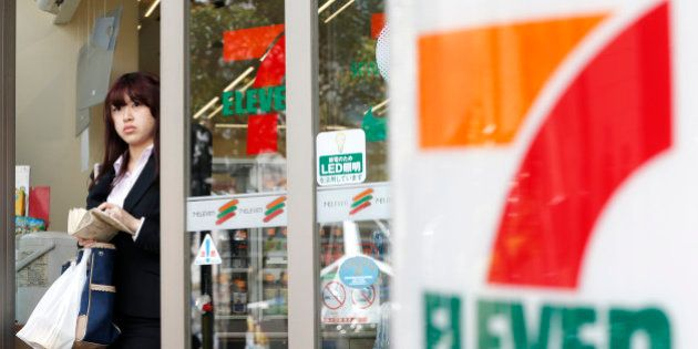 A woman exits a 7-Eleven convenience store, operated by Seven & I Holdings Co., in Tokyo, Japan, on Thursday,...