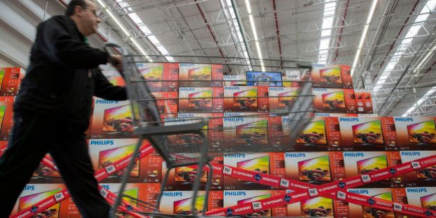 A man pushes a shopping cart past Koninklijke Philips NV televisions that are reserved for the 'El Buen...