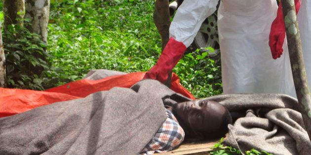 The hand of a hearth worker on a man suspected of dying from the Ebola virus before they move they body...