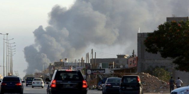 Smoke billows from an area near Tripoli's international airport as fighting between rival factions around...