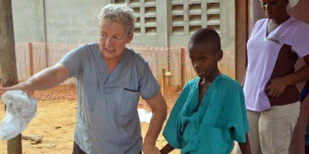 A 10-year-old boy walks with a doctor from Christian charity Samaritan's Purse, after being taken out...