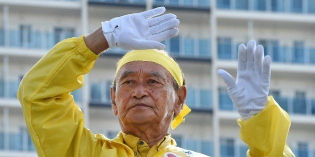 Incumbent governor Hirokazu Nakaima waves to people during his stumping tour for the Okinawa gubernatorial...