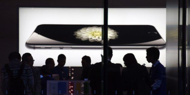 Store attendants help customers at an Apple store selling the iPhone 6 in Beijing on October 23, 2014....
