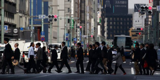 Pedestrians cross a road in the Ginza district of Tokyo, Japan, on Monday, Nov. 17, 2014. Japan unexpectedly...