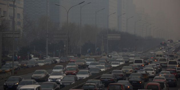 Traffic moves along a street shrouded in haze in Beijing, China, on Friday, March 15, 2013. China's new...
