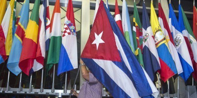 Workers at the US Department of State add the Cuban flag at to the display of flags inside the main entrance...