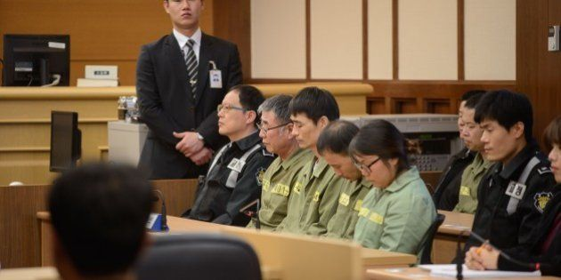 Sewol ferry captain Lee Jun-Seok (3rd R) sits with other crew members inside a a court room in Gwangju...