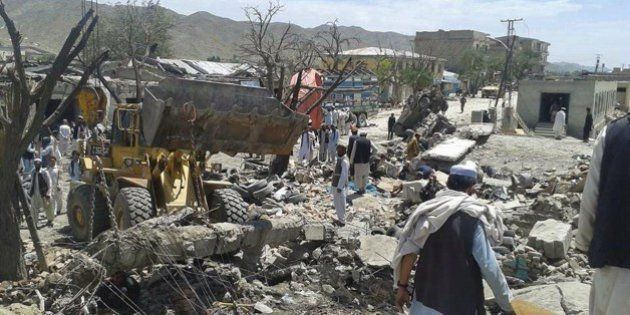 A loader removes debris as Afghans look on at the scene of a suicide attack at a market in Urgun district,...
