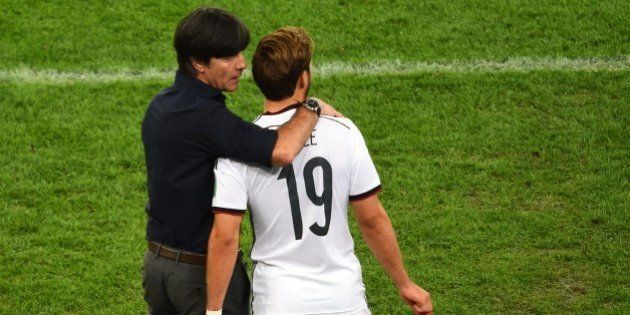 Germany's coach Joachim Loew (L) speaks with Germany's forward Mario Goetze as he comes on to play during...