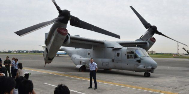 A US Marine Corps MV-22 Osprey is displayed in front of a hangar during a change of command ceremony...