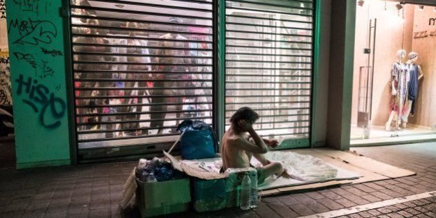 A homeless man sits on the sidewalk in front of a shop in downtown Athens on July 6 2015. Greeks declared...