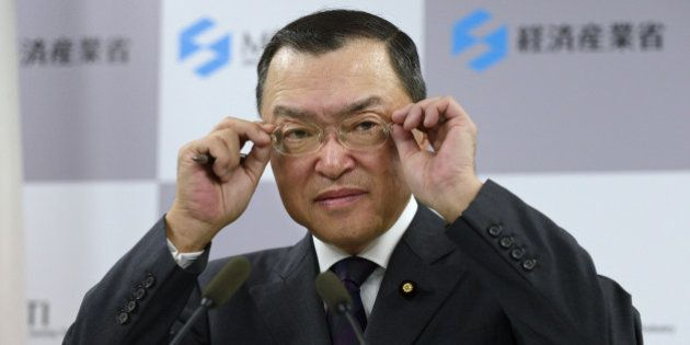 Yoichi Miyazawa, Japan's new trade and industry minister, adjusts his glasses during a news conference...