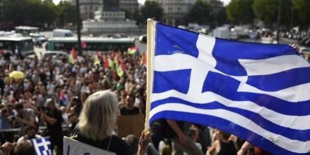 A protester holds a Greek flag as she takes part in a rally in support of the people of Greece at the...