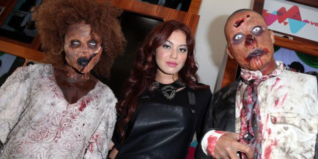 LOS ANGELES, CA - OCTOBER 31: VEVO Singer Guinevere (C) poses with two 'zombies' at her live performance...
