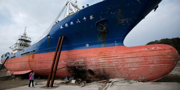 A woman looks at a vessel swept inland by the tsunami following the Great East Japan Earthquake in Kesennuma,...
