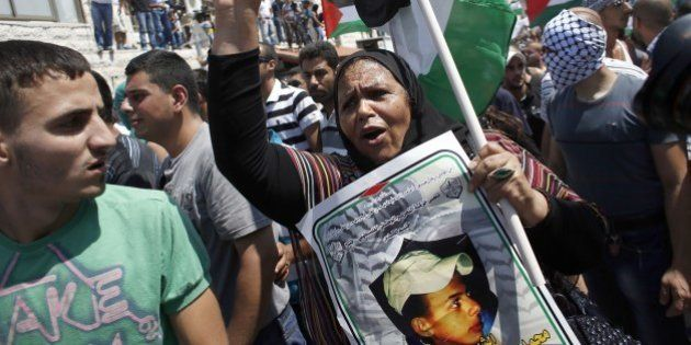 Mourners rally for the funeral of Palestinian youth Mohammed Abu Khder, 16, as they carry his body to...