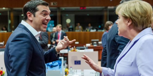 Greek Prime Minister Alexis Tsipras, left, speaks with German Chancellor Angela Merkel during a round...