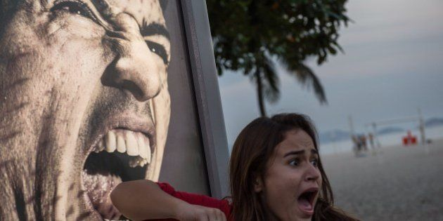 A tourist jokes in front of an advertisement with the portrait of Uruguay's forward Luis Suarez at Copacabana...