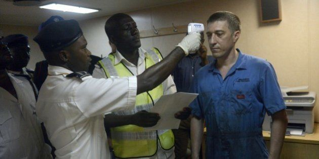 Health officials takes the body temperature of an Ukrainian sailor on the MV Pintail ship, as they check...
