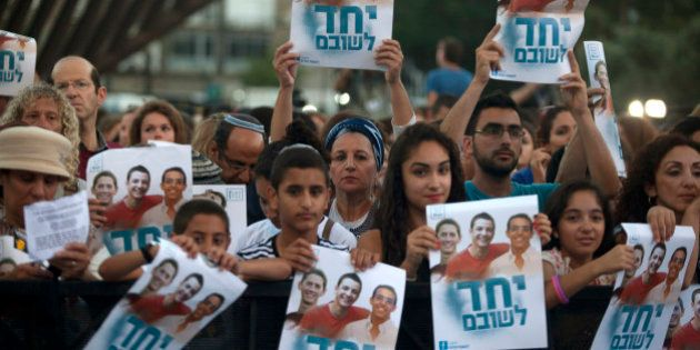 TEL AVIV, ISRAEL - JUNE 29: (ISRAEL OUT) Israelis hold a poster showing the three missing Israeli teenagers,...