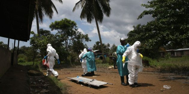 MONROVIA, LIBERIA - OCTOBER 10: An Ebola burial team dresses in protective clothing before collecting...
