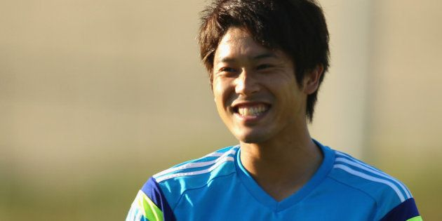 ITU, BRAZIL - JUNE 12: Atsuto Uchida laughs as he watches on during a Japan training session at the Japan...