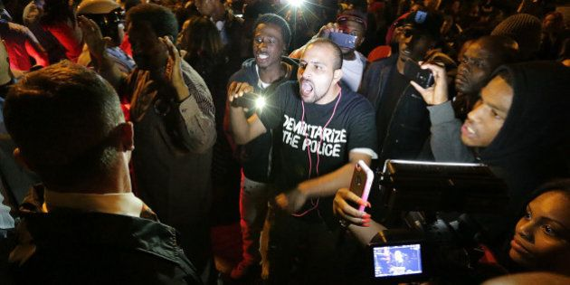 Bassem Masri, center, a man who has live streamed many of the protests in Ferguson, Mo., confronts a...