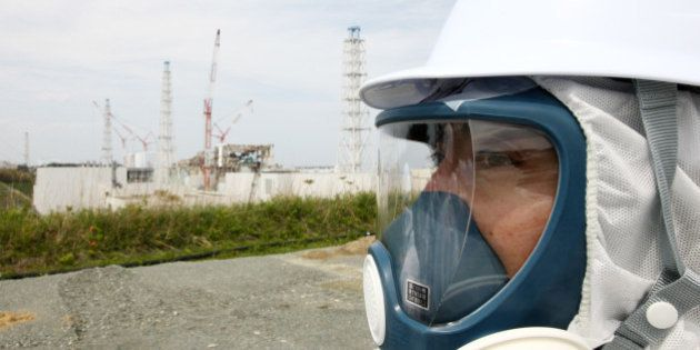 A member of the media, wearing a protective suit and a mask, stands in front of Tokyo Electric Power...