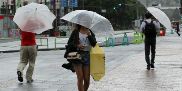 HIMEJI, JAPAN - OCTOBER 13: Pedestrians walk in the wind and rain delivered by Typhoon Vongfong on October...