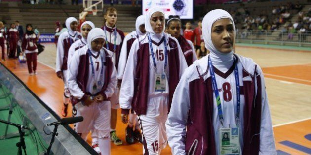 This photo taken on September 24, 2014 shows members of the Qatar women's basketball team walking off...