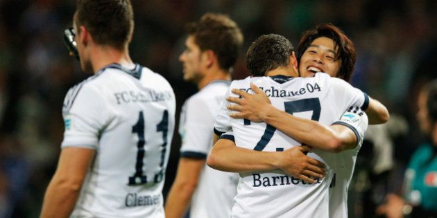 BREMEN, GERMANY - SEPTEMBER 23: Atsuto Uchida of Schalke celebrates with team mate Tranquillo Barnetta...