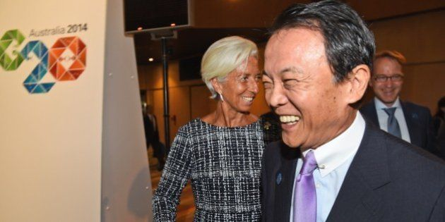 Head of the IMF Christine Lagarde (C) greets Japan's Minister of Finance Taro Aso (R) at the G20 Finance...