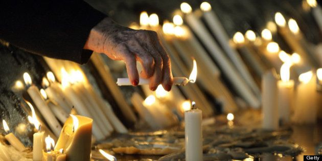A woman lights a candle at the Basilica and National Sanctuary of Our Lady of Aparecida -which will be...