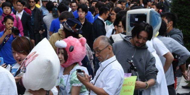People wait for the release of the iPhone 6 in front of an Apple store in the Ginza shopping district...