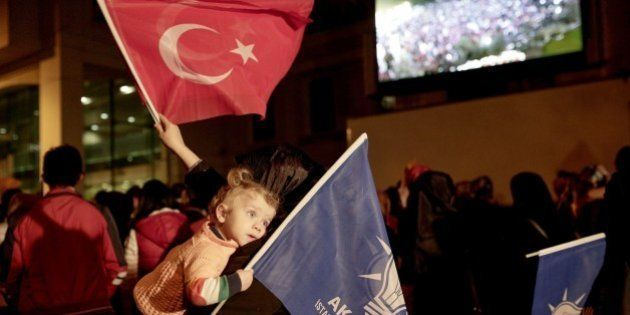 Justice and Development Party (AKP) supporters wave party and Turkish flags at Istanbul`s AKP headquarters...