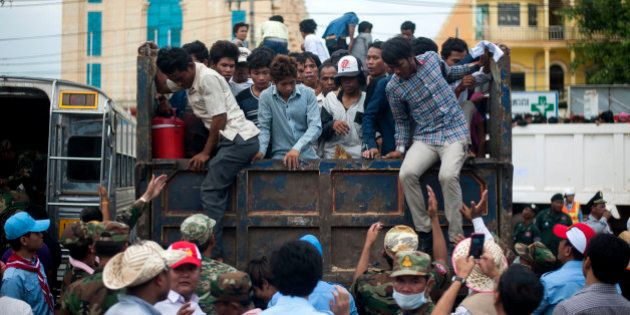 POIPET, CAMBODIA - JUNE 17: Cambodian workers get off a truck after crossing the Thai border on June...